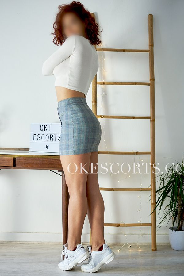 Amanda posando con cartel de OK!Escorts
